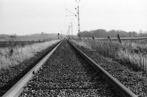 järnvägsspår med kontaktledningsstoplar, i bakgrunden Billeberga